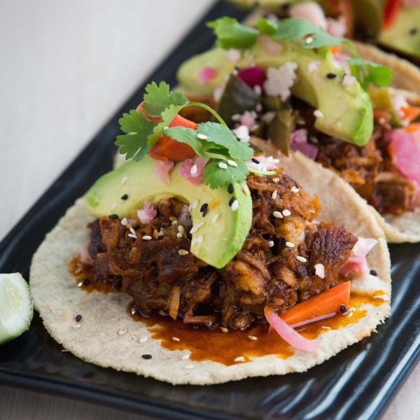 The pork shoulder tacos are fresh tortilla filled with tender pork, chile-mezcal sauce, avocado, seasonal pickles, cilantro and pepitas.