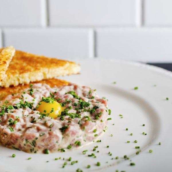 "Steak Tartare ""Classique"" is tender, ultra-fresh beef served with chives, toast points and the cutest little omega-rich quail egg ever."