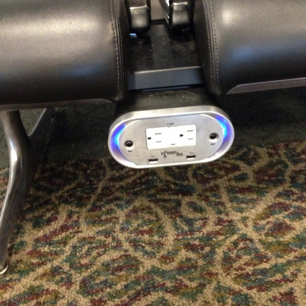 Look for seats with power outlets underneath them. Usually up against walls.