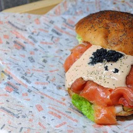"""¿Quien dijo que una hamburguesa no puede ser un manjar? Os presentamos La del Mar, hecha con salmón ahumado noruego, caviar negro, philadelphia, pepinillo, rúcula, cebolla, tomate y salsa """"La Tropa""""."""