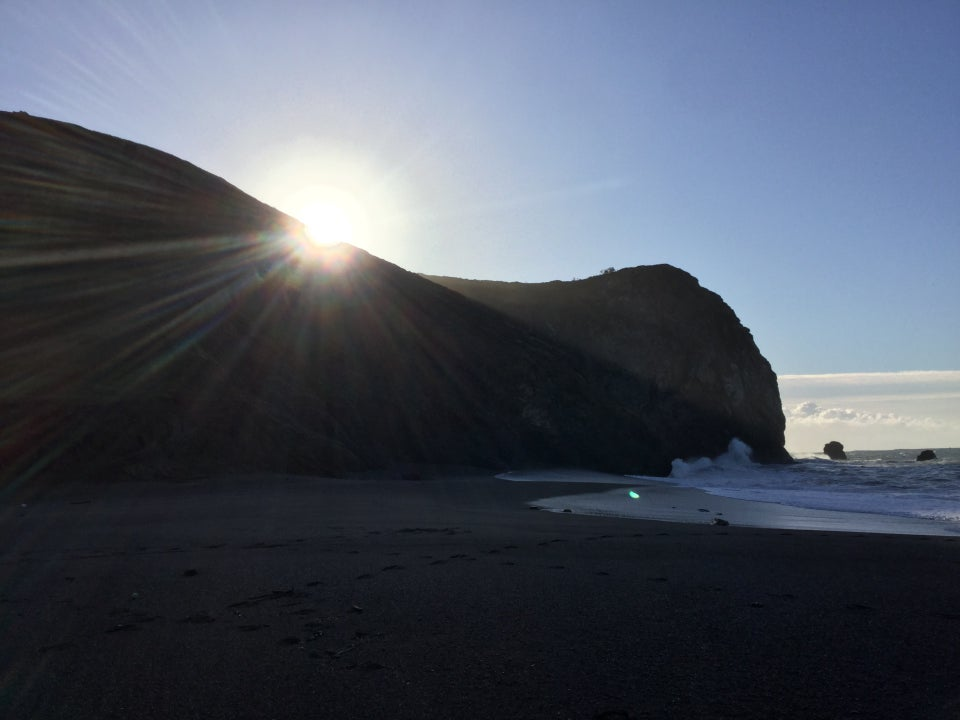 The sun rising over a hill just to the south of Tennessee Valley beach, sunbeams illuminating the surf, with most of the beach on the shadow of the hill.