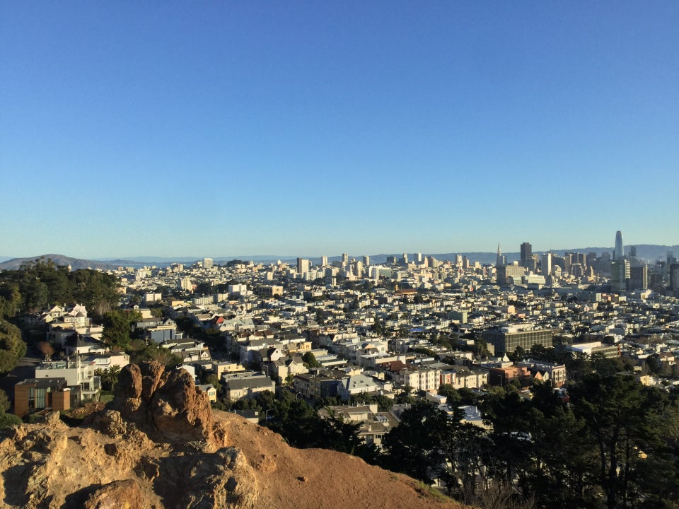 Clear blue sky over distant North East Bay hills in the distance, San Francisco's tall buildings and downtown on the horizon, with more buildings nearer, trees from Buena Vista Park on the left, a rocky outrcopping from Corona Heights park immediately in the foreground.