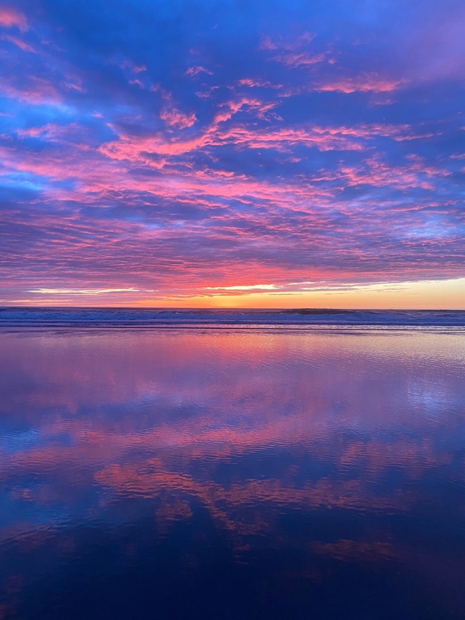 Blue, purple, pink clouds lighting up a post-sunset sky above an orange yellow horizon and distant Pacific Ocean waves crashing on a shore, wet sand in the foreground reflecting the beautiful sky.