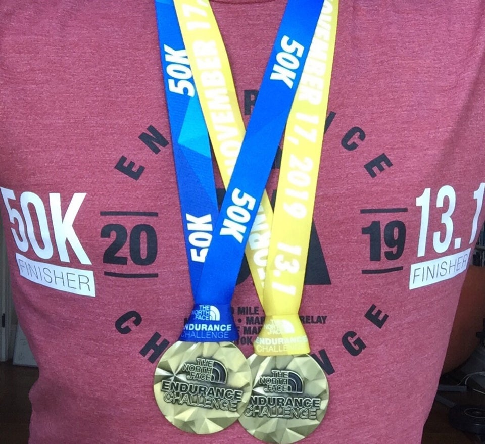 Wearing The North Face Endurance Challenge 2019 t-shirt with both 50k Finisher and 13.1 Finisher heat decals added, and 50k with blue ribbon and 13.1 Half Marathon with yellow ribbon medals hanging from the neck.