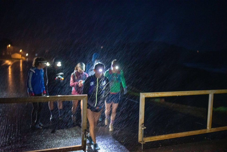 Half a dozen runners wearing headlamps, rain gear, and shorts, starting a run at a gate in the darkness, their headlamps lighting up the pouring rain, Rodeo Beach in the background.