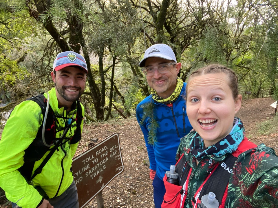 Bryan, Tantek, and Krissi standing in front of a sign to the start of the Skyline to Sea trail, with a forest behind them.