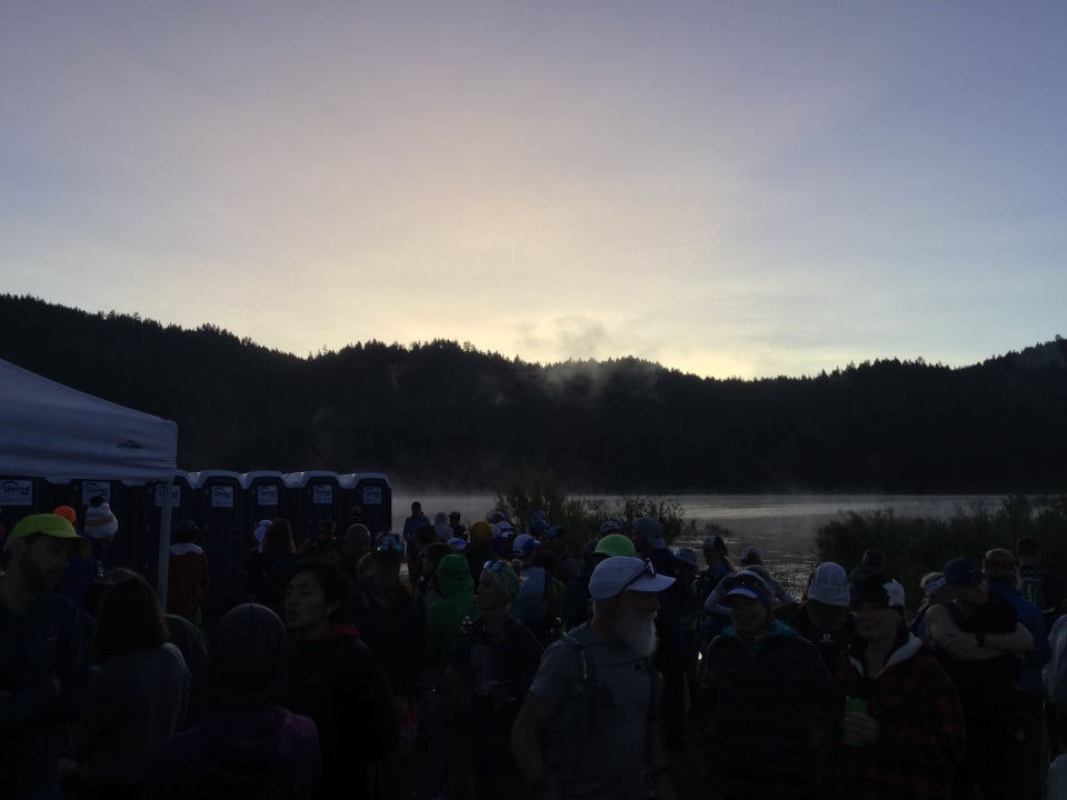 Spooner lake before dawn, the sky brightening above dark hills, mist over the lake, TRT racers in the foreground