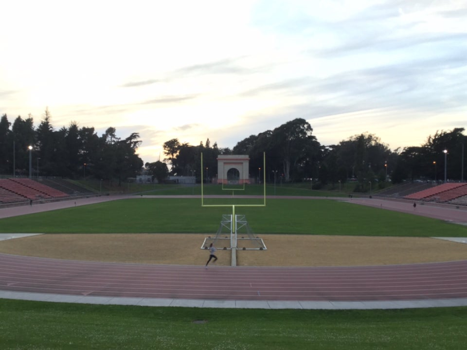 A bright sky overexposed by the setting sun lighting up clouds, trees in the distance above Kezar Stadium, football field goals aligned in the green field, a single woman runner sprinting in lane 1 on the track.