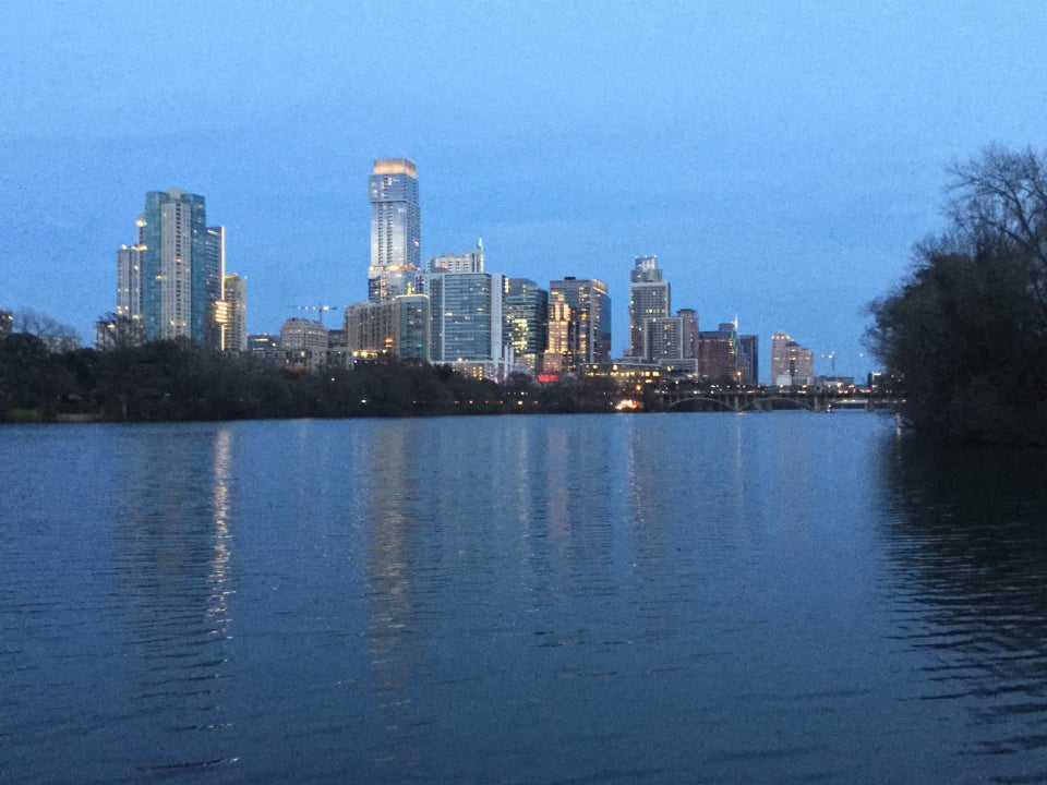 Dusk view of the west part of downtown Austin, reflected in the river below.