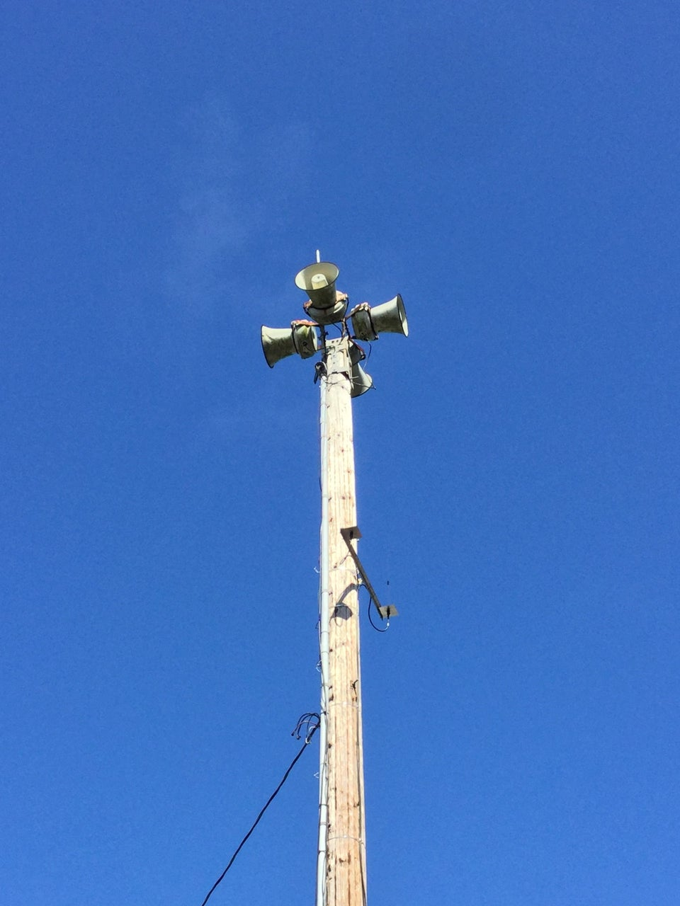 Old air raid sirens on a tower in front of blue skies.