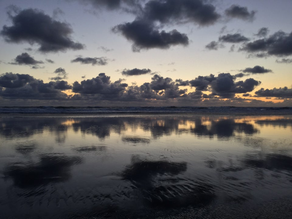 Scattered dark clouds above cumulus clouds over the ocean, waves breaking upon a wet shore, reflecting the clouds and post-sunset sky, bits of orange in the gaps between the clouds on the horizon.