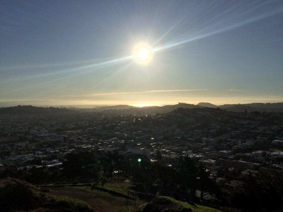 Sun over the bay, with sunbeams extending to the sides, and a sunlit bay, East Bay shoreline partially hidden by haze, San Francisco buildings in the middle, and the base of Corona Heights park below.