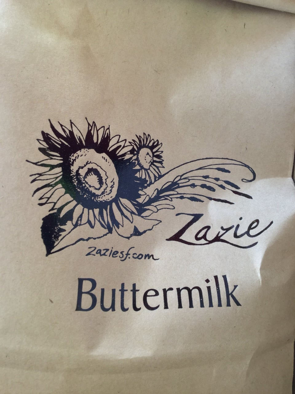 Bag of Zazie buttermilk pancake mix, with a stylized black & white graphic of sunflowers, Zazie, website, and Buttermilk text on the bag.