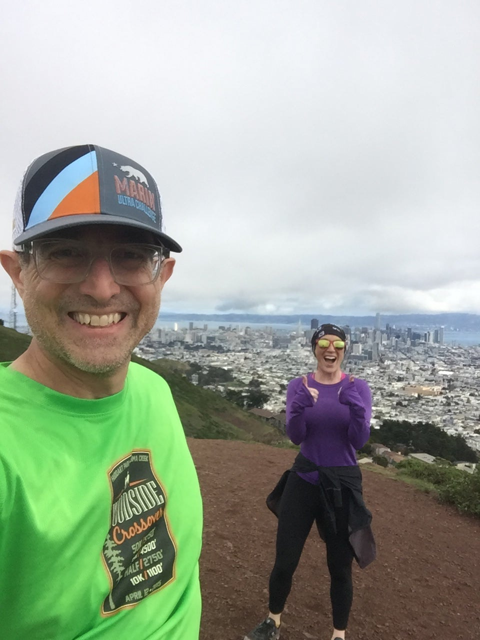 Tantek and Courtney smiling, more than six feet apart from each other, on top of the North Peak of Twin Peaks, with downtown San Francisco in the distance behind them.
