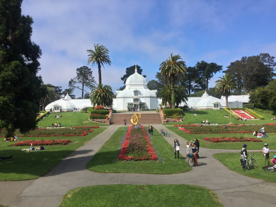 The Conservatory of Flowers buildings with the flower gardens in the foreground under a blue sky with scattered clouds.