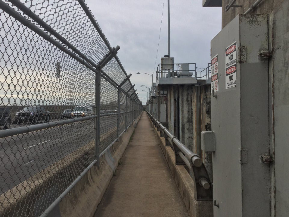 On top of the Longhorn dam, chainlink fencing on the left with the roadway on the other side, and the dam structures and warning signs on the right, the path across the river in between them.