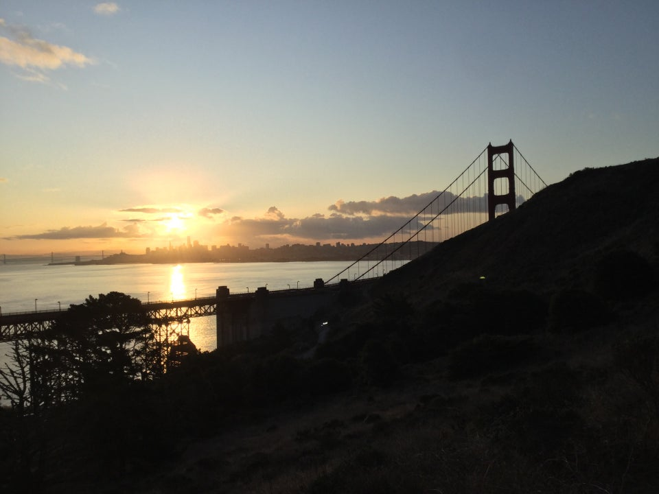 Sunrise over the San Francisco skyline, lighting up the bay below, north span of the Golden Gate Bridge and tower, backlit trees and the Battery Spencer hill in the foreground.
