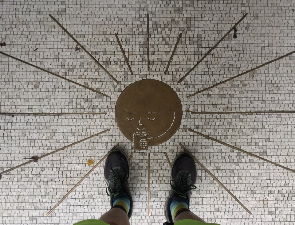 Looking down at a mottled white mosaic entryway with a brass sun-with-a-face seemingly sipping a cup of coffee, brass segment sunbeams radiating outward.