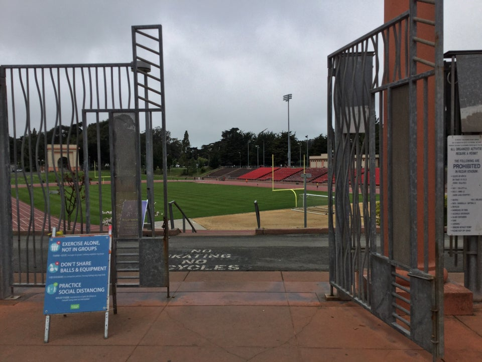 Open entrance gate to Kezar Stadium and track, themselves visible beyond the gates, a warning sign just to the left of the open gate.