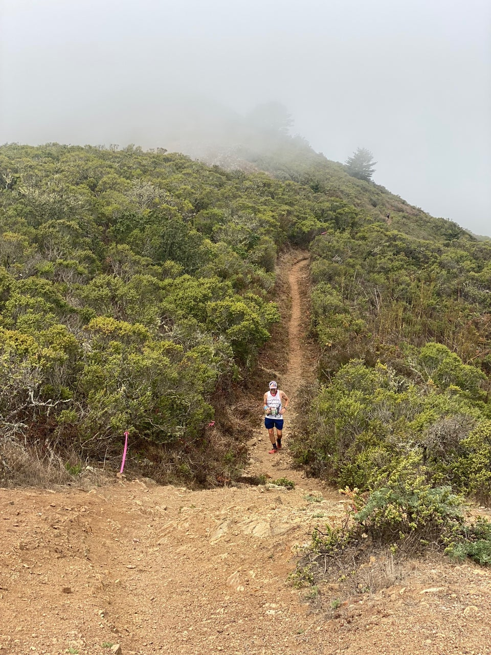 Fogged-in view of a lush green hillside, narrow singletrack trail cutting up from the right and approaching the center, with Tantek power hiking uphill, grinning, water bottle in right hand, holding his side with his left.