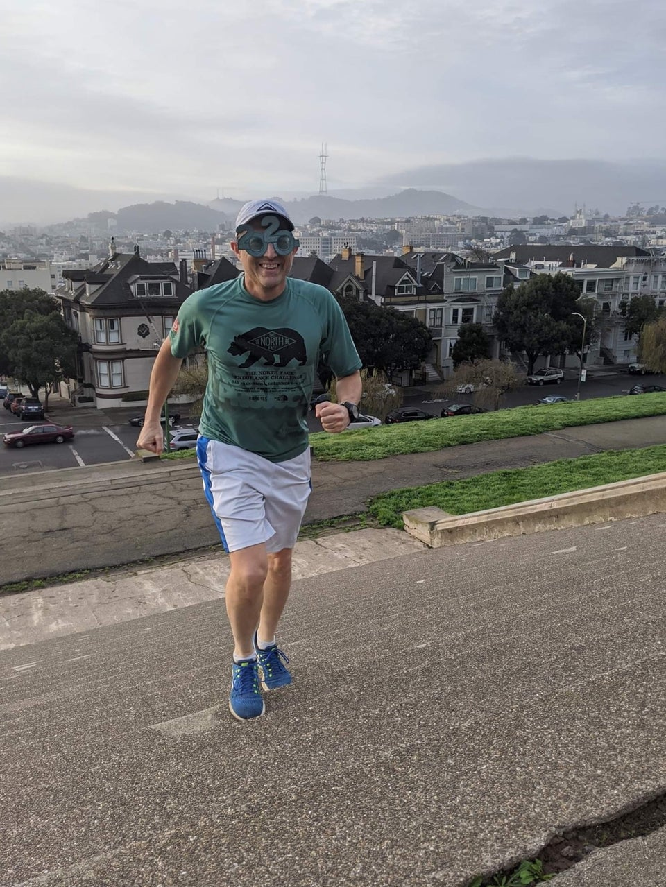 Tantek in running t-shirt, shorts, and cap, also wearing a year 2020 costume glasses running up Alta Plaza park stairs.