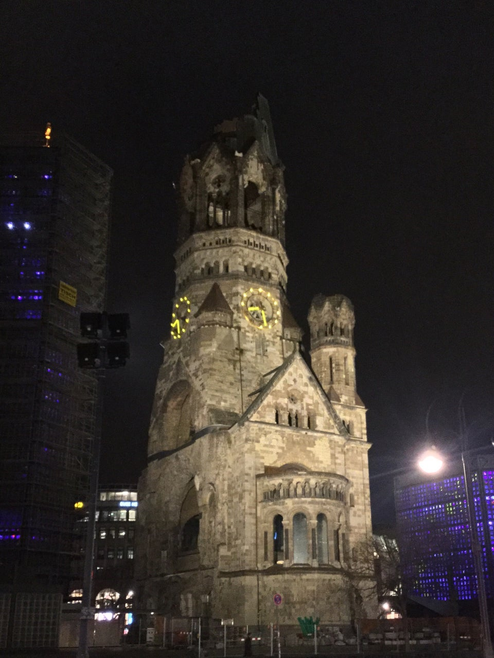 A old church with a severely damaged spire at night, with a light-up clock on it, with modern buildings with lights on both sides.