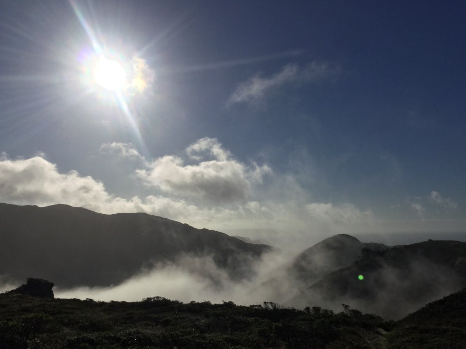 Sun shining with sunbeams in a blue sky with scattered mostly low hanging clouds behind hills, fog pouring into the valley below, and nearby green hillside sloping downard.