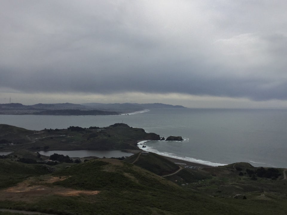 Cloudy skies over the Pacific Ocean, looking down on Rodeo Beach and lagoon, green hills on both sides of them.