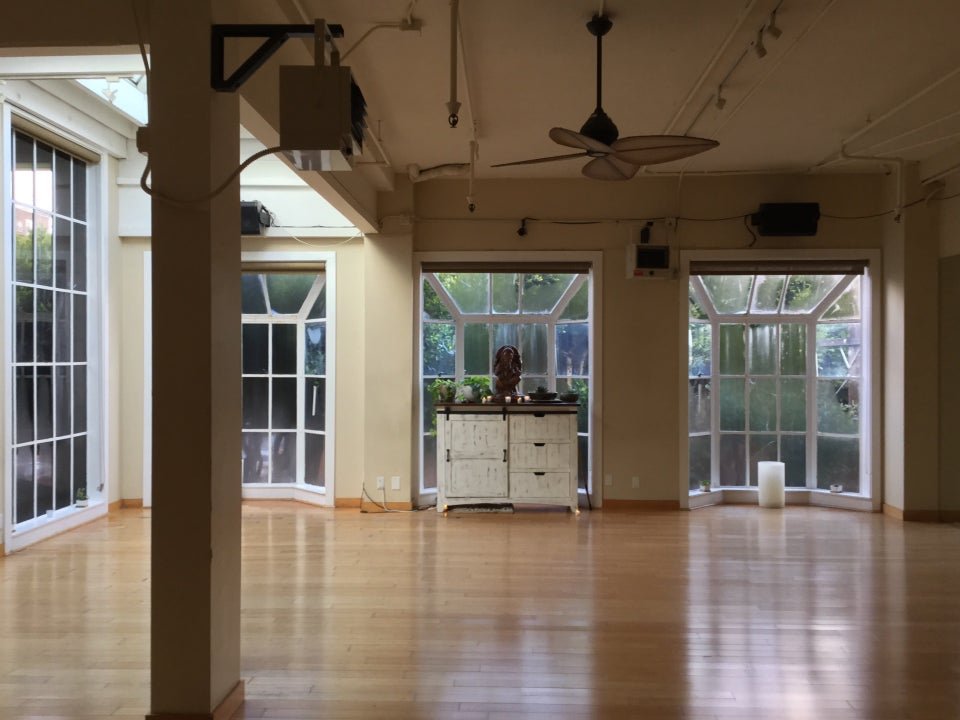 Yoga studio workout room with a heater and fan on the ceiling, a single support post on the left, steamed up multipaned bay windows across most of the walls letting in light and trees visible just beyond them, a small wide medium height cabinet set back in the center bay window with an alter to a small Ganesha statue on top, surrounded by small candles.