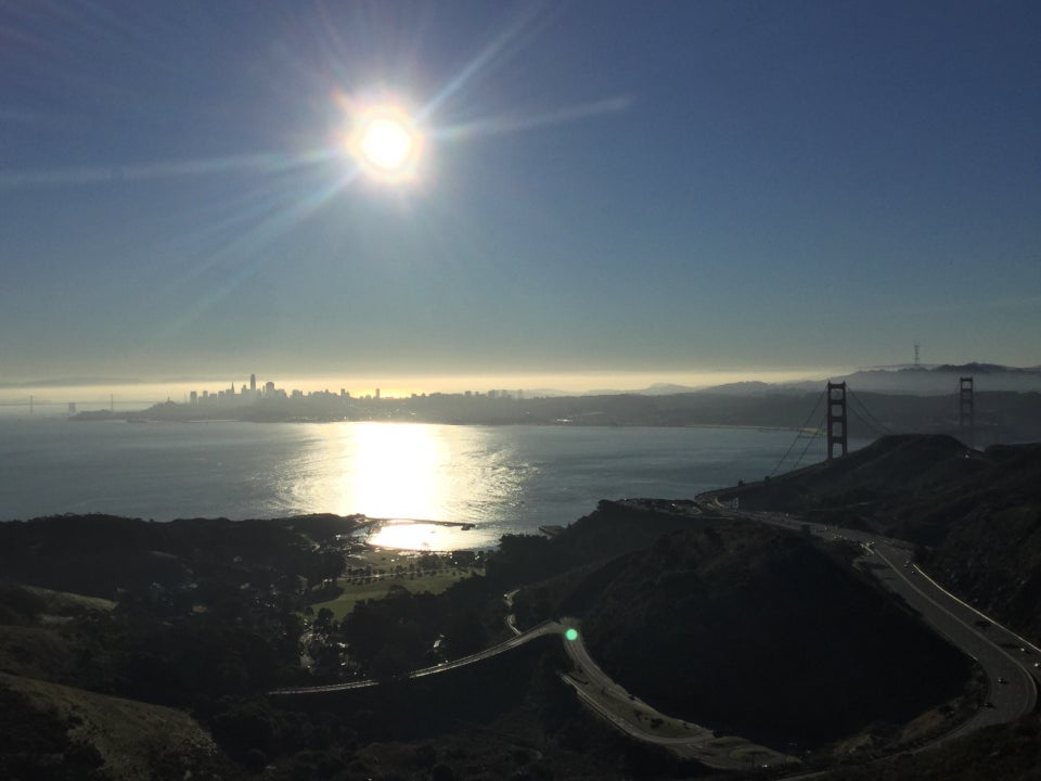 The sun shining brightly in a clear sky above a thing layer of haze behind a bit of the Bay Bridge and the San Francisco skyline from downtown to Sutro tower, Golden Gate bridge towers visible just below, a sunlit bay, and Marin headlands in the foreground.