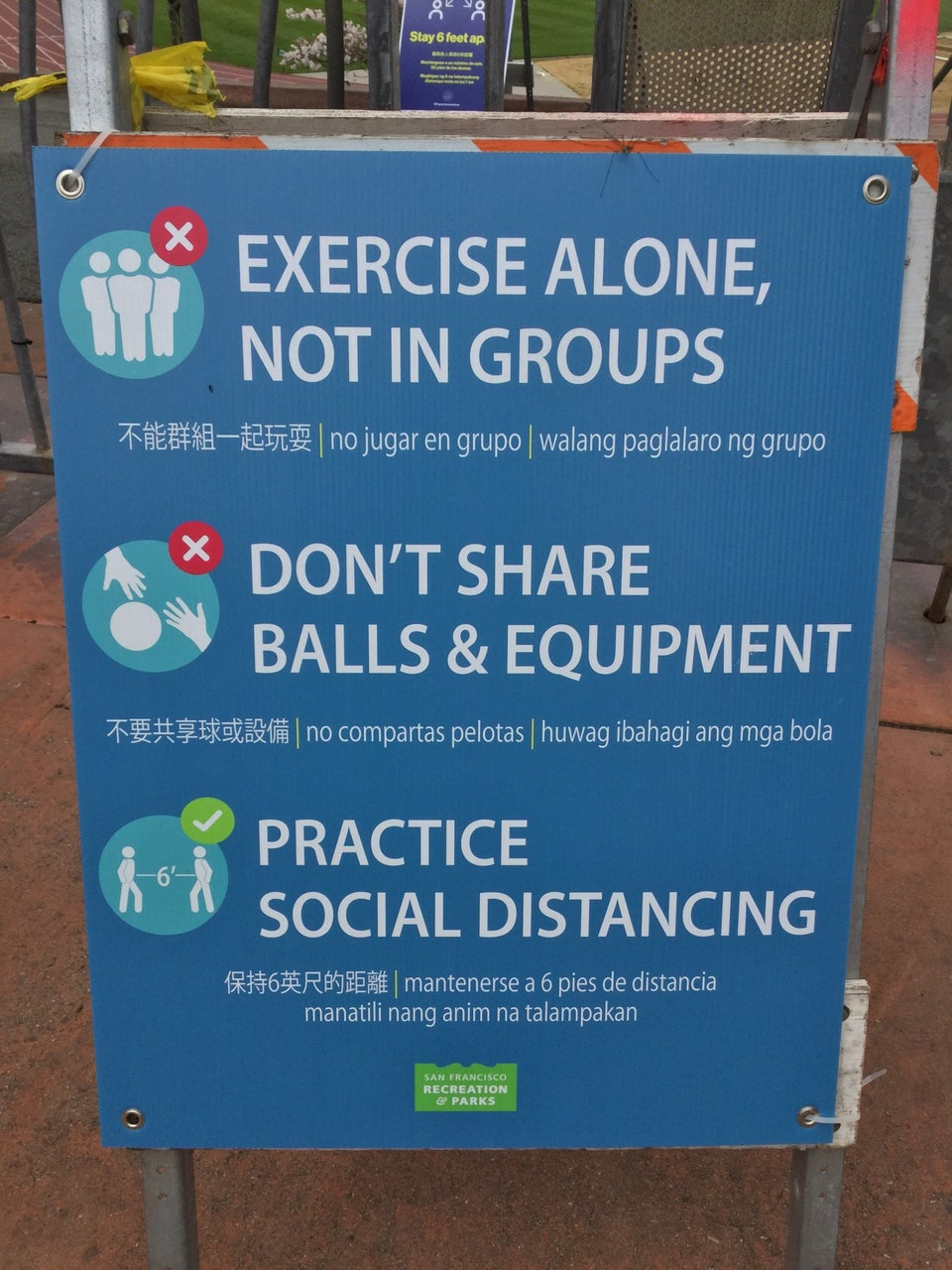 "Close-up of a sign with three statements, each translated into Chinese, Spanish, and Filipino, stating ""EXERCISE ALONE, NOT IN GROUPS"", ""DON'T SHARE BALLS & EQUIPMENT"", and ""PRACTICE SOCIAL DISTANCING"", below those a small San Francisco Recreation & Parks logo."