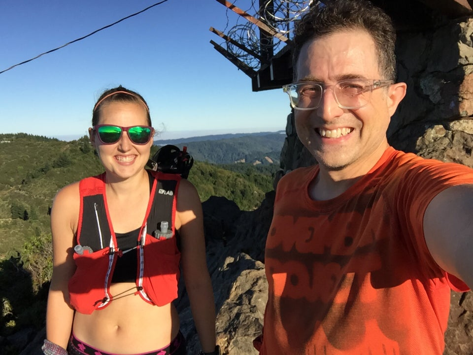 Sunlit Krissi and Tantek at Mount Tam's East Peak with the West Peak and hills behind them