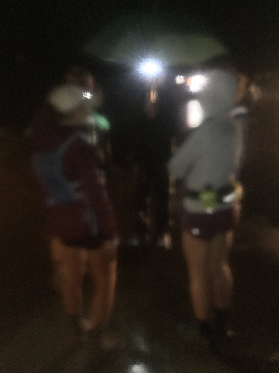 Blurry image of a few runners in rain gear and shorts on both sides of Bryan wearing a lit headlamp holding a green umbrella.