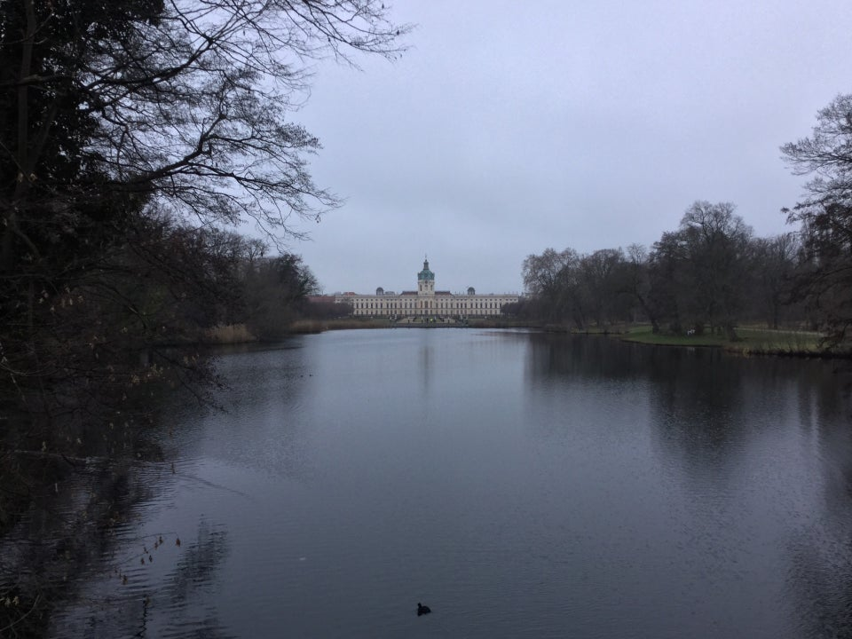 Overcast skies over a distant Castle Charlottenburg, a big pond in front of it, lined by leafless trees on either side.