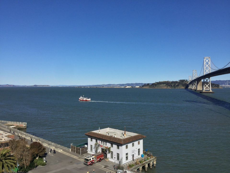 Bright blue skies above a clear distant East Bay, Treasure Island, and part of the Bay Bridge, above the bay with a small powered boat making its way leaving a wake, part of the Embarcadero with a firestation, a fire engine parked right outside, ready to go.
