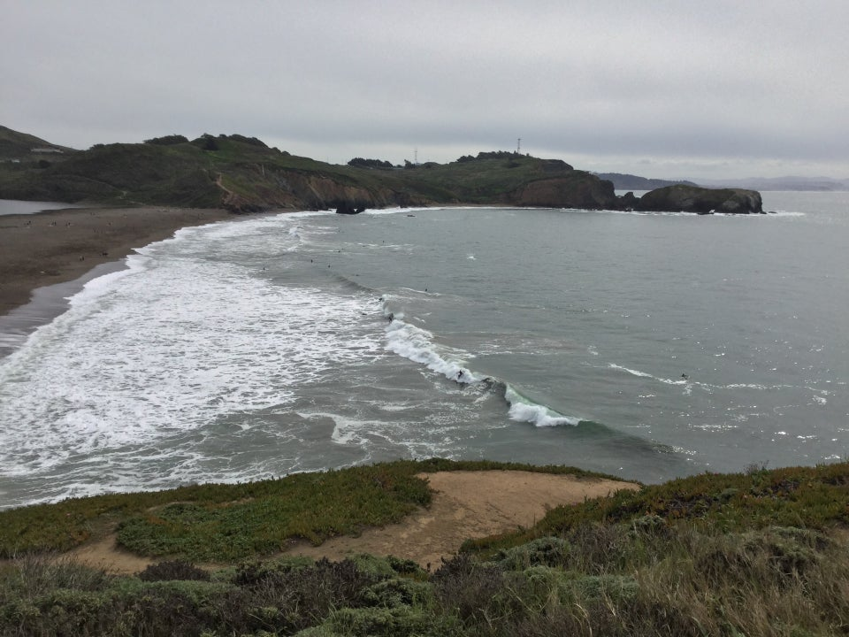 Rodeo Beach with large waves breaking, several surfers catching the waves and surfing.