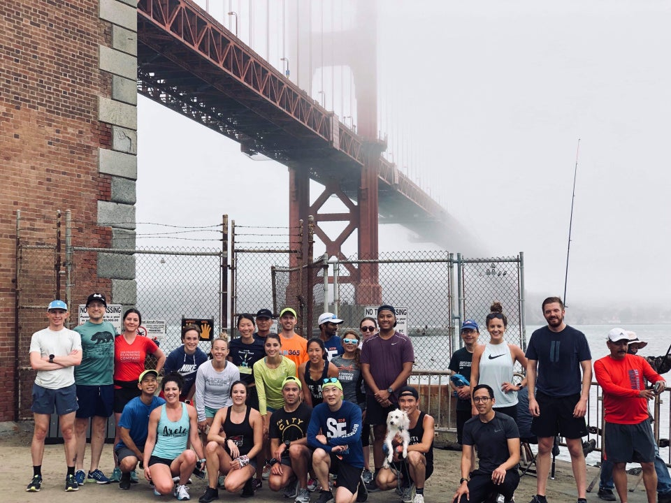 Runners lined up standing and kneeling in front of the Hoppers Hands fence with the Golden Gate Bridge in the background disappearing into the fog