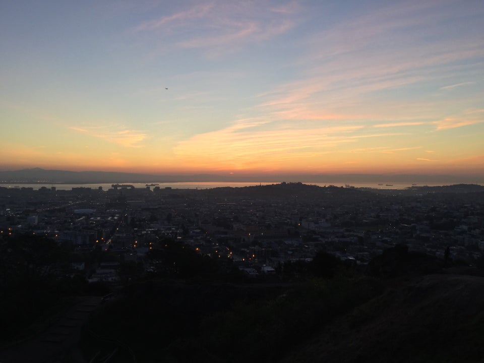 Pink and orange wisps of cotton candy clouds in the light blue pre-dawn sky above a horizon glowing yellow and orange over East Bay Hills, a sliver of bay visibe below it, then distant San Francisco hills, buildings with lights, and nearby hills and trails in darkness.