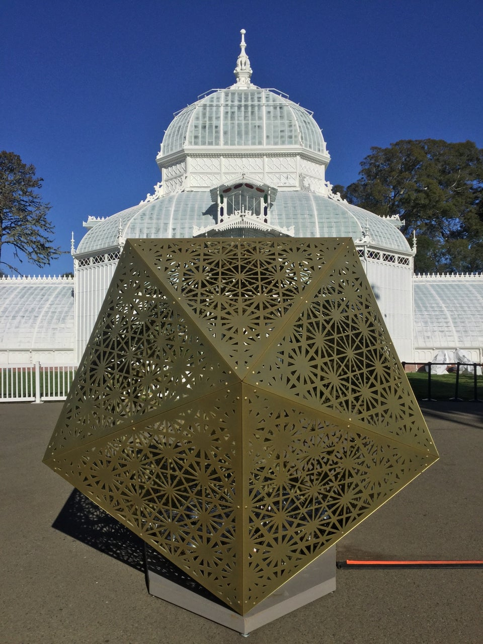 Artistic bronze colored large metal icosahedron with hexagonal patterns cut into its faces in front of the Conservatory of Flowers building.