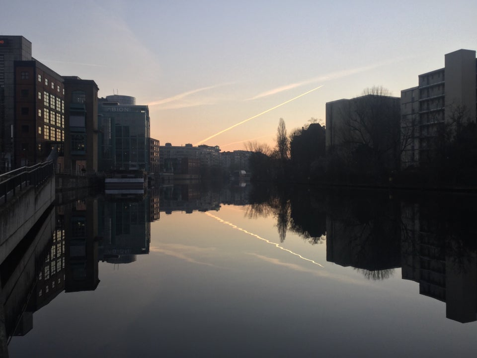 Clear sky with one contrail, slight orange glow towards the middle horizon, above buildings on both sides, trees on the right side of the river Spree which is showing their reflections.