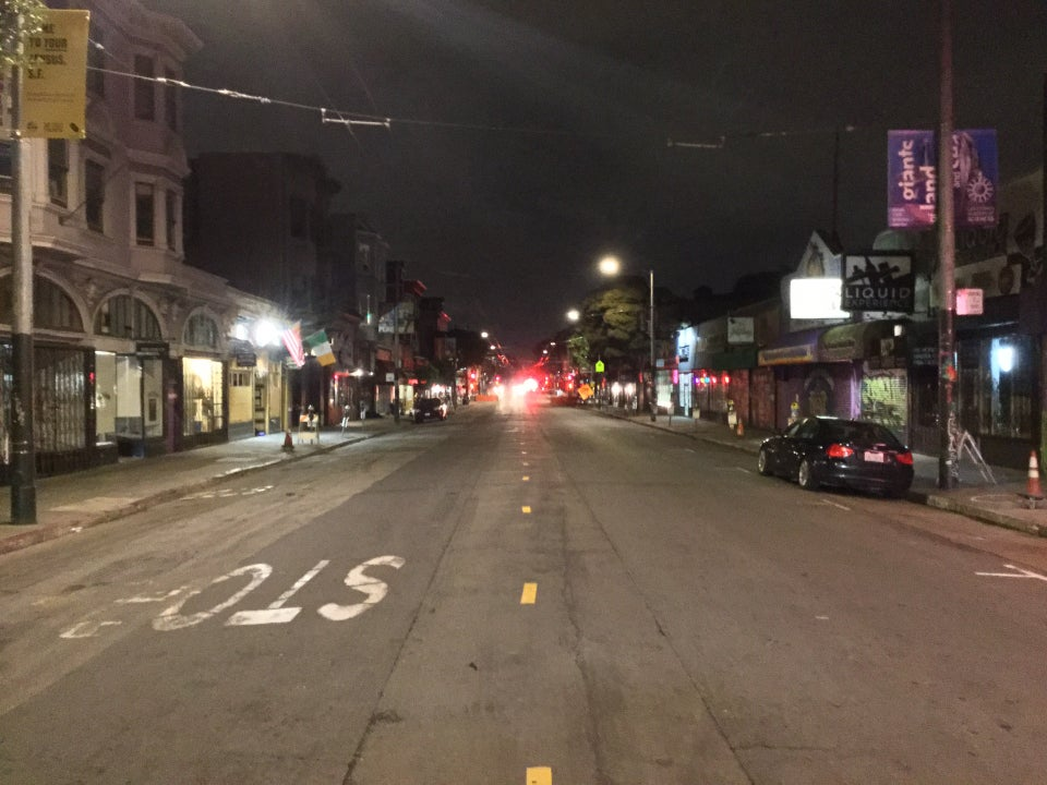 Looking down Haight Street at night, with only a couple of parked cars, and one more on the street with headlamps in the distance, with no one on the sidewalks.