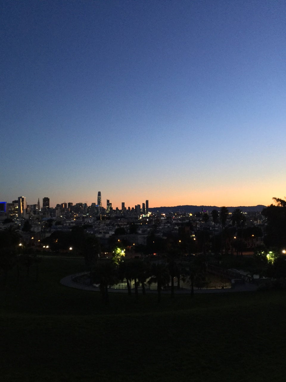 Clear blue to orange pre-dawn gradient sky above the San Francisco skyline in the distance behind a barely visible Dolores Park, a few paths and trees lit in by lamps.