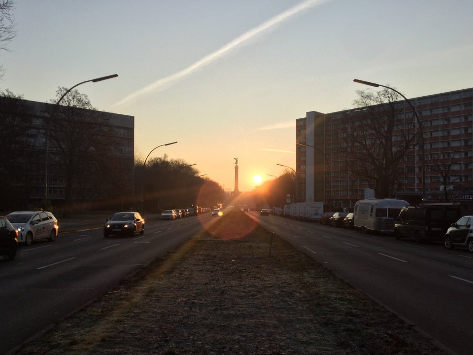 Clear sky with one dissipating contrail above an orange glow above the Berlin Victory Column and the sun rising in the distance, buildings on either side of the street, with cars going back and forth in the two directions separated by a wide median.