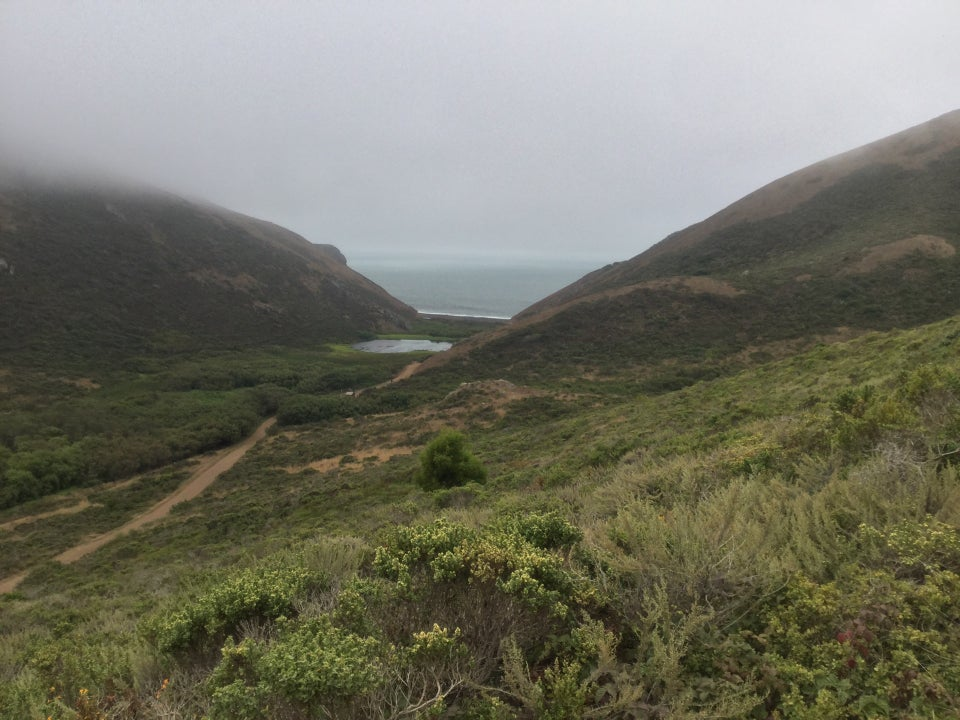 Tennessee Valley as seen from Coastal Fire road descent: green hills, Tennessee Valley trail winding them past a lagoon to the beach between two cloud covered hilltops.