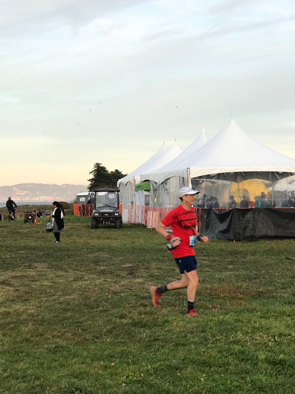 Tantek running the last few meters on uneven Crissy field towards the North Face Endurance Challenge finish line, finishing area tents in the background.