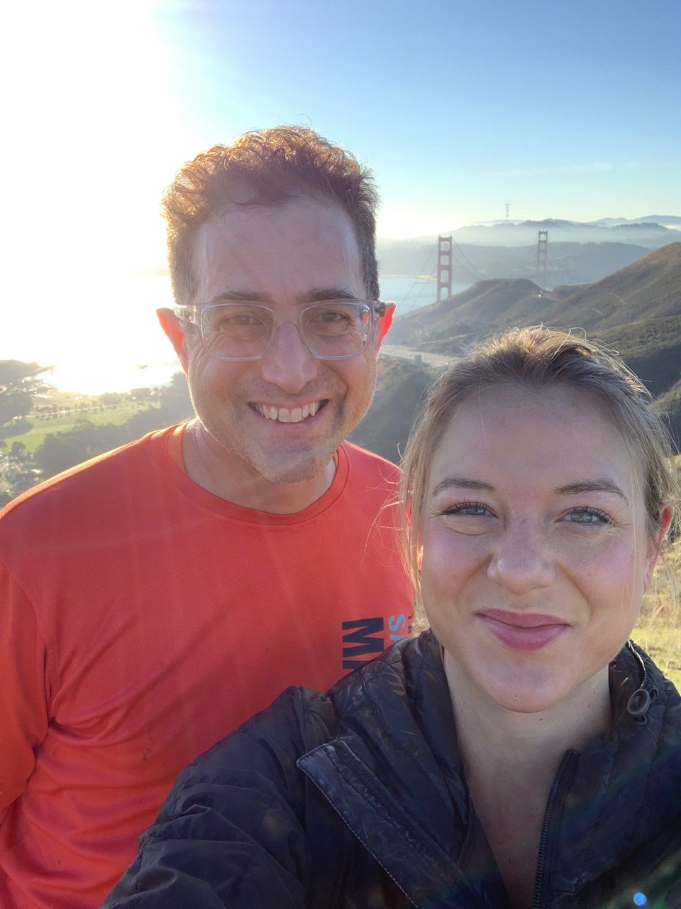 Emily taking a selfie of herself and Tantek with bright sun behind them, and the Golden Gate bridge towers poking above the Marin Headlands.