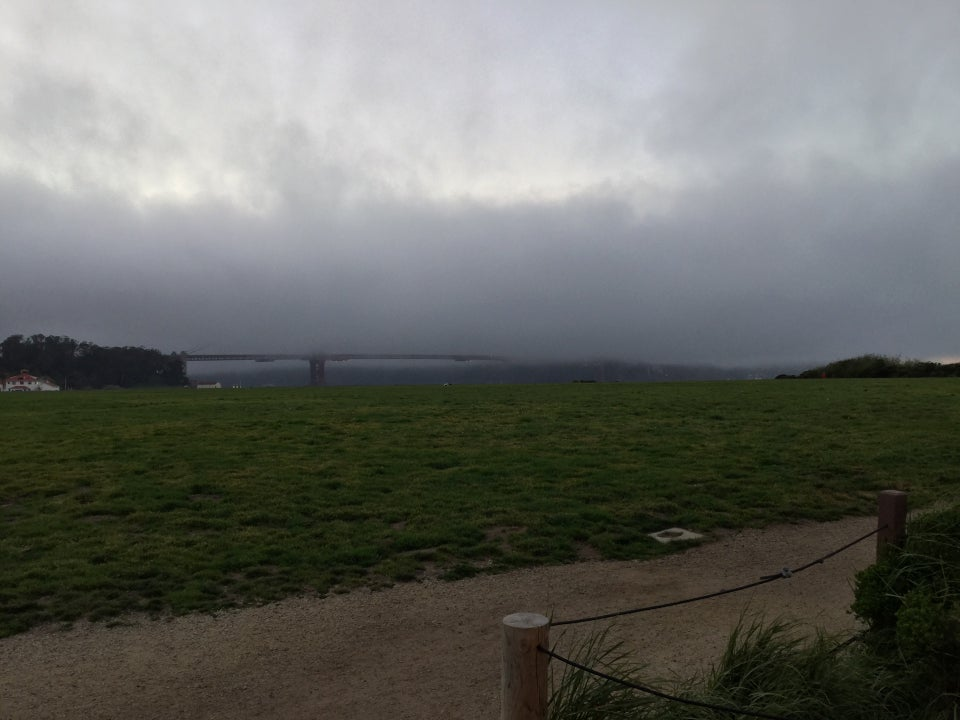 Heavy fog covering all but the bottom edge of the Golden Gate Bridgy, above a very green Crissy field in the foreground, with a gravel path immediately in front of that.