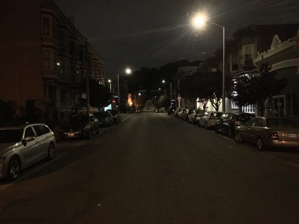 Intersection of Frederick and Downey streets at night, looking eastward, everything is dark except the aforemention things at Frederick and Ashbury, the trees of Buena Vista Park are very dark, outlined by the gray sky above them.