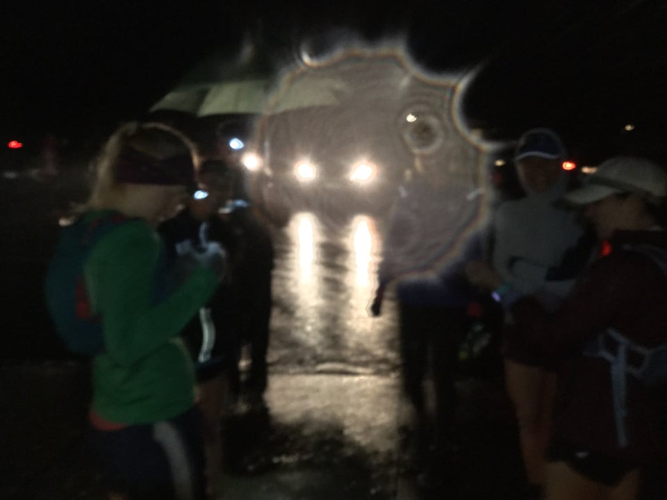 Runners clustering in the rainy darkness, Bryan with a green umbrella, backlit by headlamps from cars in the parking lot, also lighting up a drop of water on the camera lens.