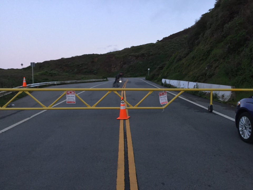 Temporary yellow metal barricade blocking the full width of Twin Peaks Boulevard with an orange cone in front of it, and NO STOPPING TOW AWAY signs attached to it in a couple of places, behind it a bicyclist swerving towards the right edge of the gate, and the hill up to Twin Peaks itself.